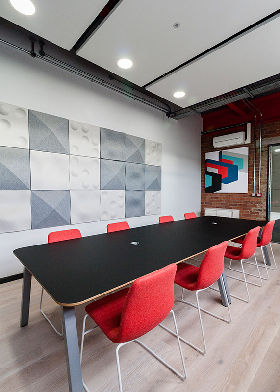 This meeting room for the Formica European head office features acoustic wall panels, dampening the sound within the room, and feature-artworks (also designed by Contents Design) which are made from Formica's own products. The table top is a finger-print-proof, self-healing laminate. - Interior design by Contents Design