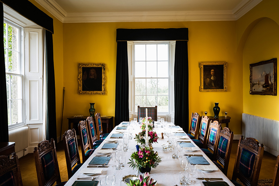 Dining room with deep saffron walls, plaid upholstery and velvet drapes - Galgorm Castle, Ballymena, N. Ireland - Interior design for restoration and refurbishment: Johanne O'Neill
