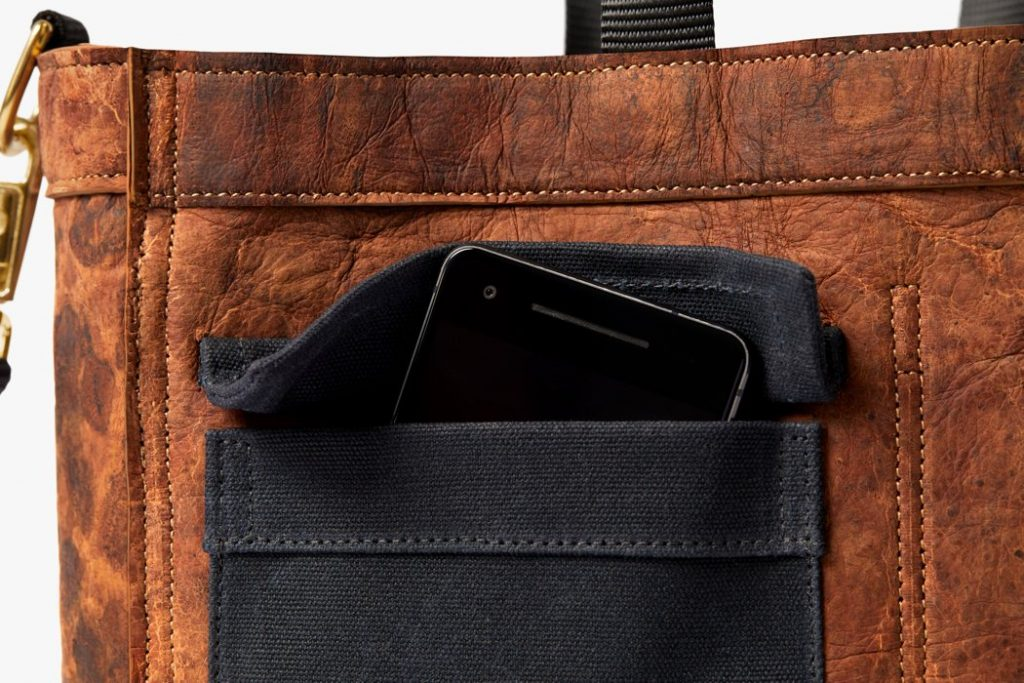 Detail of the Driver bag made from mycelium leather in Mylo™ Unleather developed by Bolt Threads and designed by Chester Wallace. Image shows texture and softness of the material with contrasting buckskin-style Unleather with black detailing.